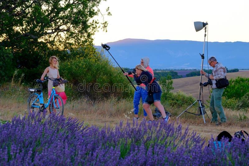 Fotografo ed assistente di illuminazione che prende le immagini di una giovane donna con la bicicletta immagine stock libera da diritti