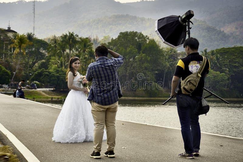 Fotografo ed il suo assistand che fanno la foto del ritratto per la sposa che tiene i fiori fotografia stock