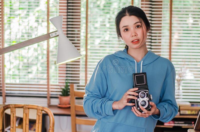 Fotografo femminile d'annata alla moda che tiene la sua vecchia macchina fotografica gemellata della lente al suo petto come comp fotografia stock