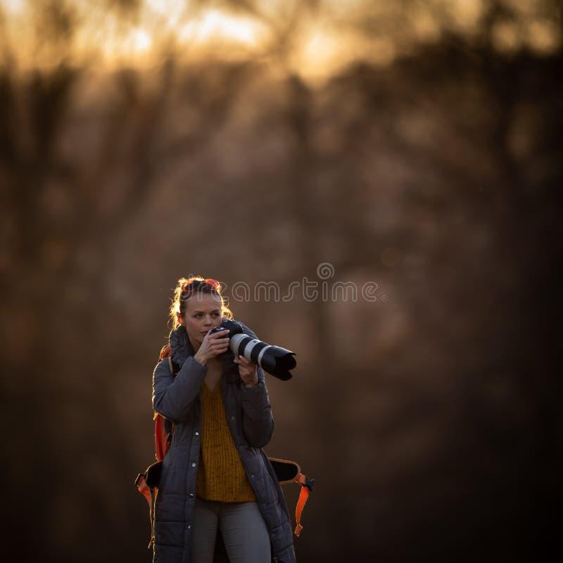 Fotografo femminile sveglio con la sua macchina fotografica del dslr che prende le foto all'aperto fotografia stock libera da diritti