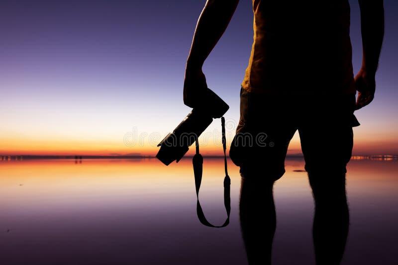 Fotografo maschio che prende immagine con la macchina fotografica del dslr sulla spiaggia al tempo di tramonto immagine stock libera da diritti