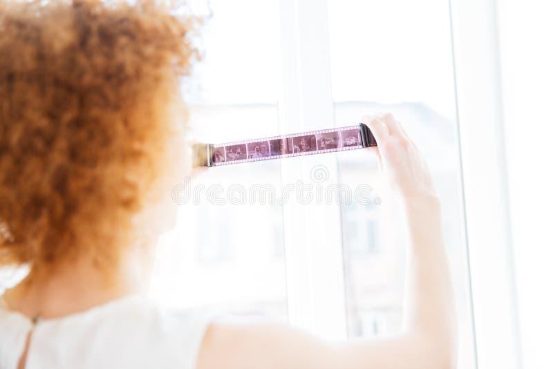 Fotografo riccio della donna che esamina pellicola fotografica vicino alla finestra immagini stock