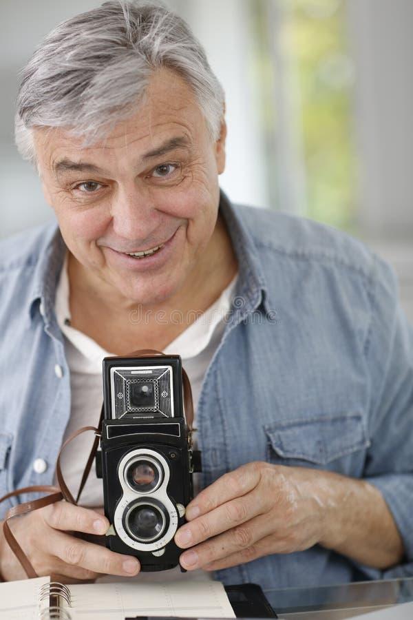 Fotografo senior che usando macchina fotografica d'annata immagini stock