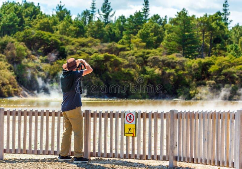 Fotografo sui precedenti dello stagno geotermico nel parco di Wai-O-Tapu, il Distretto di Rotorua, Nuova Zelanda Con il fuoco sel fotografia stock libera da diritti