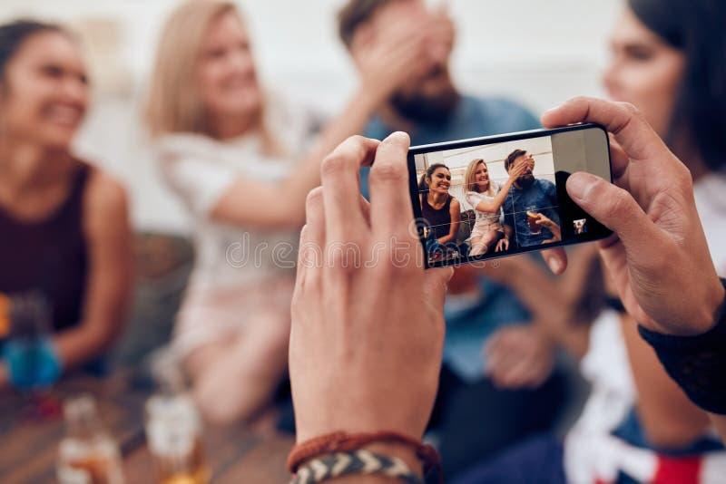 Fotografować przyjaciół przy przyjęciem z telefonem komórkowym obraz stock