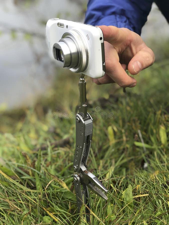 Fotografować używać improwizuję znaczy Ścisła kamera wspina się na falcowanie nożu, wtykającym w ziemię zamiast tripod T fotografia royalty free