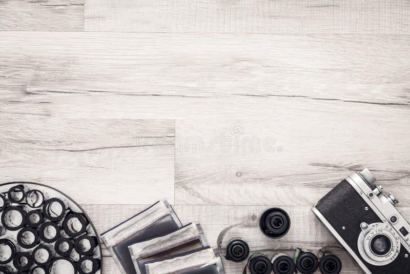 Fotografskrivbord med tappningkameran och rullar av filmen Lägenheten lägger med kopieringsutrymme arkivbilder