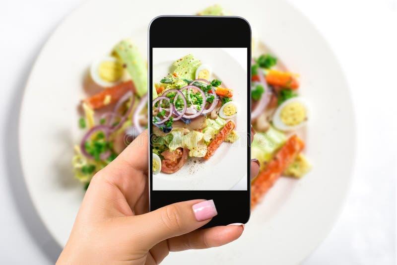 Fotografujący karmowego pojęcie - kobieta bierze obrazek świeża sałatka z sałatą, jajka, pomidory, cebulkowi pierścionki, pieprze obraz royalty free