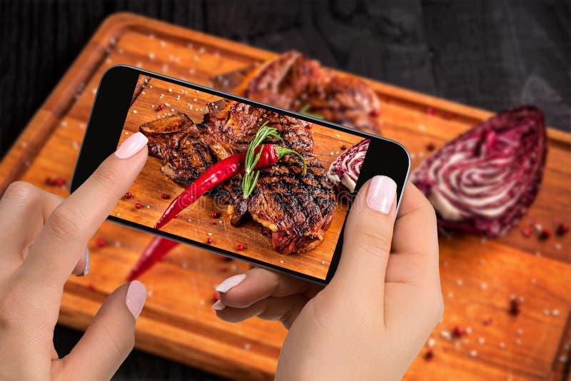 Fotografujący karmowego pojęcie - turysta bierze obrazek je wołowina stku naczynie na ciąć drewnianą deskę na smartphone zdjęcie stock