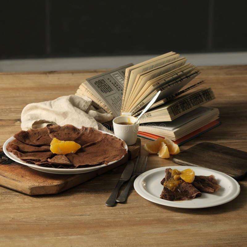 Fotographia dell'alimento Pancake del cioccolato con inceppamento arancio su un piatto di legno immagini stock libere da diritti