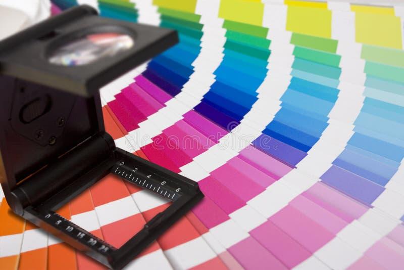 Fotographische Vergrößerungslupe und Farbenmuster stockbilder