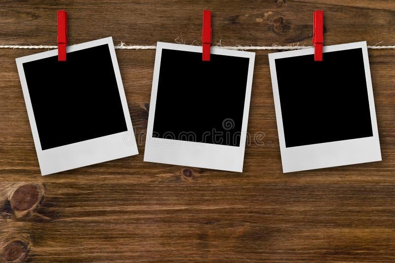 Fotokaders die op rode wasknijpers hangen stock afbeelding