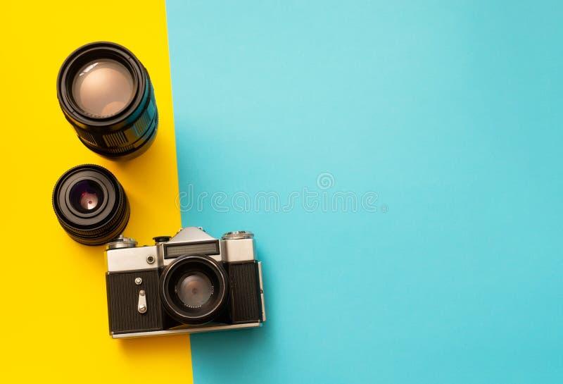 Fotokamera mit Ersatzlinsen auf blauem und gelbem Hintergrund stockfoto