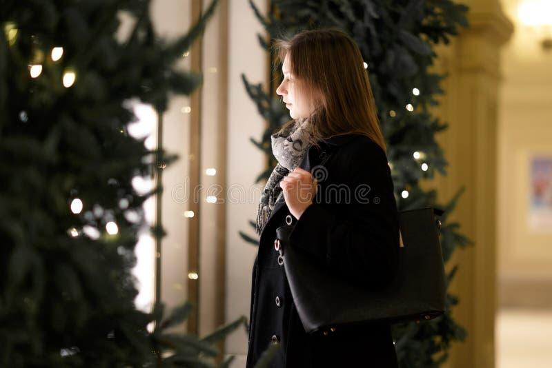 Fotokant van jonge vrouw bij winkelvenster in avond royalty-vrije stock fotografie