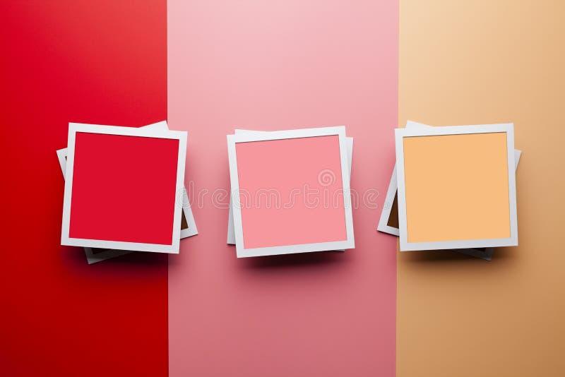 Fotomodellmall - tre pappers- fotoramar med tomma utrymmen för ditt innehåll på bakgrund för pastellfärgad färg royaltyfri foto