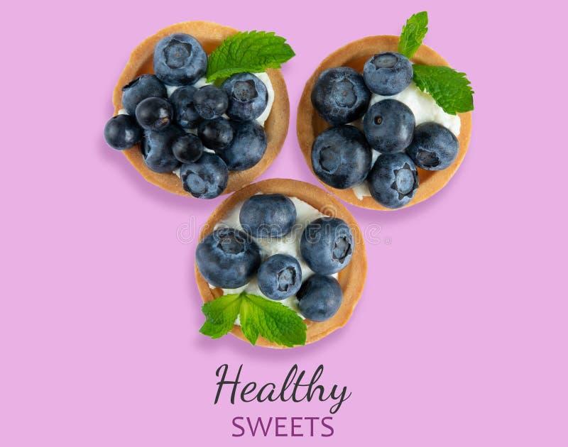 Fotomuster mit Tartlets auf einem rosa hölzernen Hintergrund Kuchen mit Beeren des Jachthafens, Blaubeere, Blaubeere mit tadellos lizenzfreies stockbild