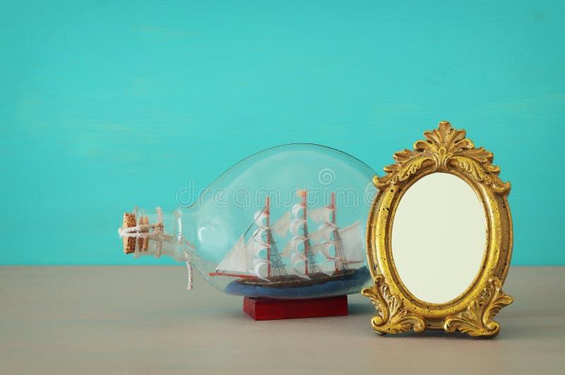 Fotorahmen der Weinlese leerer Goldnahe bei Boot in der Flasche über Holztisch Bereiten Sie für Fotografiemontage vor lizenzfreie stockfotografie