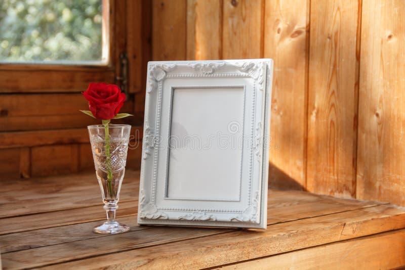 Fotorahmen und eine rote Rose lizenzfreie stockfotos