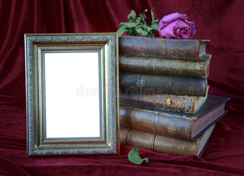 Fotorahmen und Stapel antike Bücher stockfotos