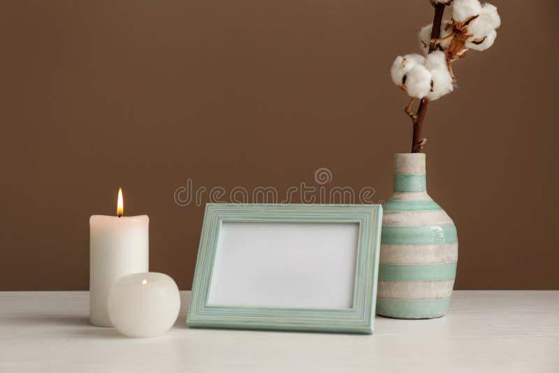 Fotoram med bomullsblommor i vas och stearinljus på den vita tabellen mot färgbakgrund royaltyfria bilder
