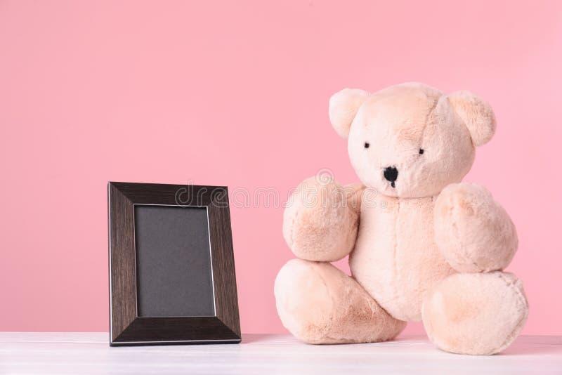 Fotoram med utrymme för text och förtjusande nallebjörn på tabellen mot färgbakgrund royaltyfri fotografi
