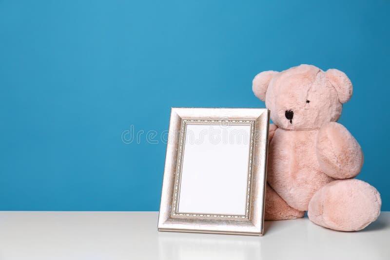 Fotoram och förtjusande nallebjörn på tabellen mot färgbakgrund Best?ndsdelar f?r barnrum fotografering för bildbyråer