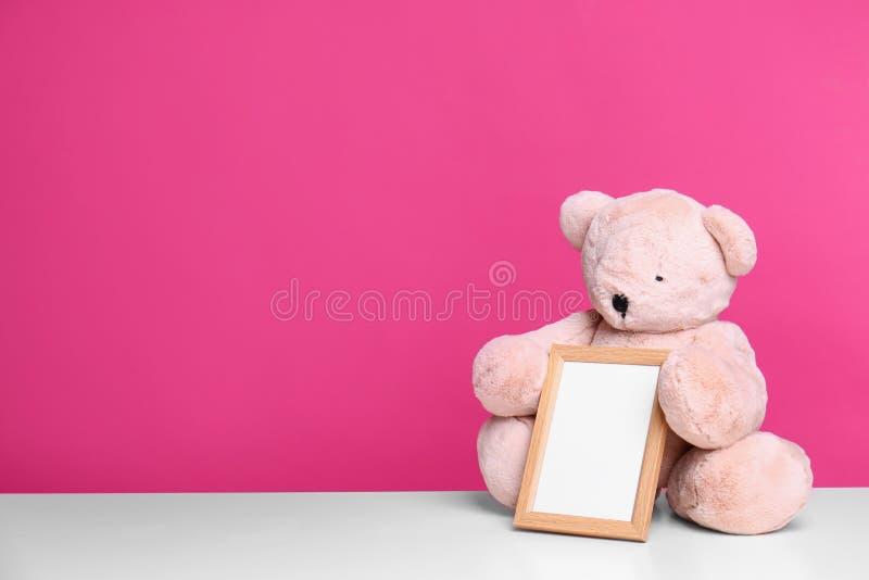 Fotoram och förtjusande nallebjörn på tabellen mot färgbakgrund Best?ndsdelar f?r barnrum royaltyfria bilder