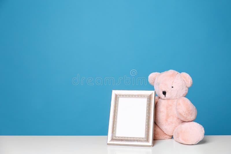 Fotoram och förtjusande nallebjörn på tabellen mot färgbakgrund Best?ndsdelar f?r barnrum royaltyfria foton