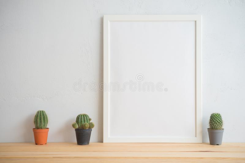Fotoram och kaktuskrukamodell med vit väggbakgrund, c arkivbild