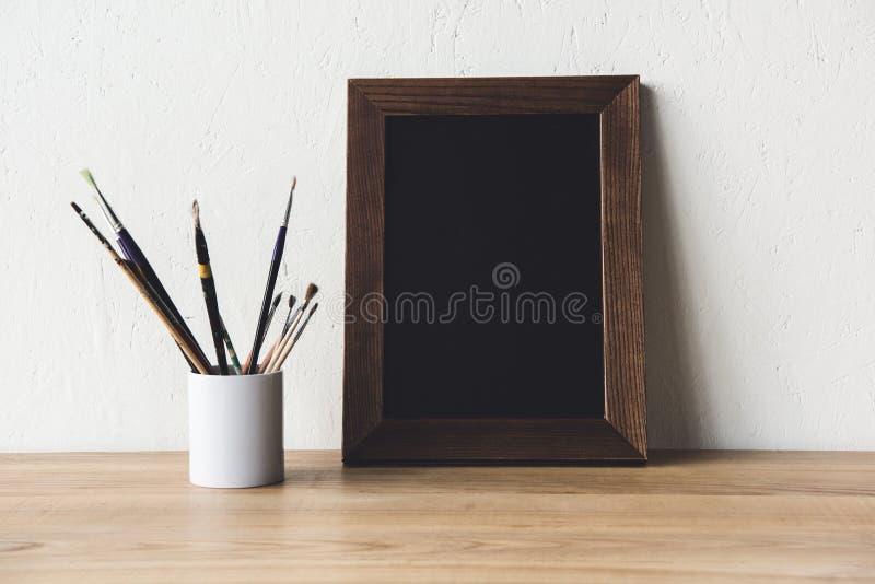 fotoram och målarpenslar på tabletopen royaltyfria foton