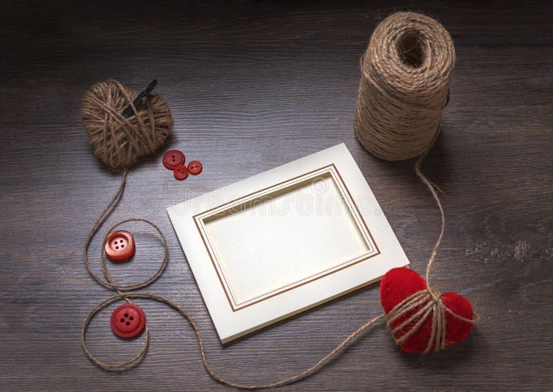 Fotoramar och handmaded hjärtor för valentindagleksak över träbakgrund Bästa sikt med kopieringsutrymme fotografering för bildbyråer