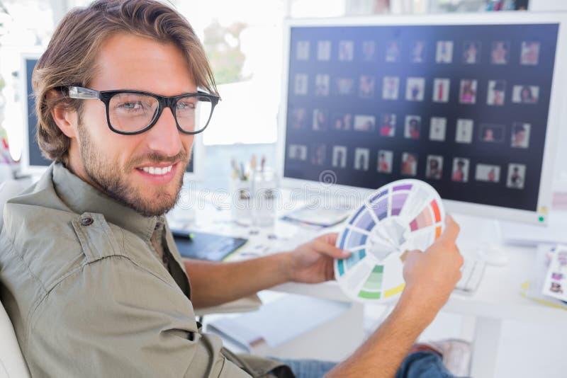 Fotoredacteur die kleurenwiel bekijken en aan glimlach draaien stock afbeeldingen