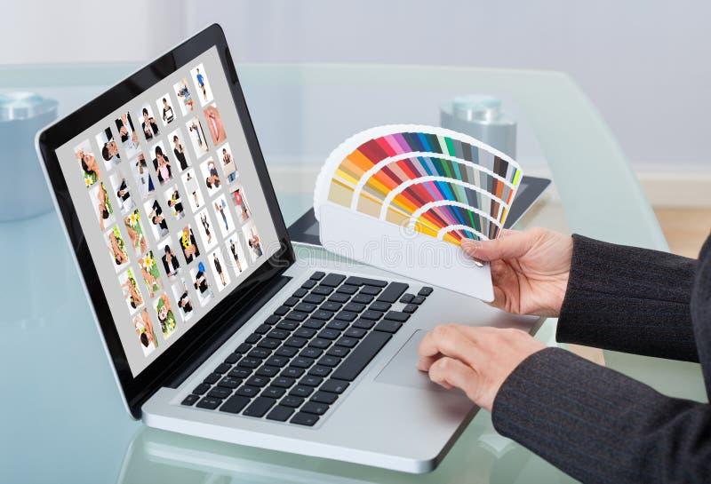 Fotoredacteur die laptop met behulp van bij bureau stock fotografie
