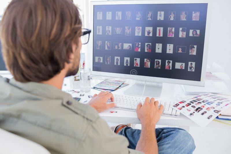 Fotoredacteur het bekijken duimnagels op computer royalty-vrije stock afbeeldingen