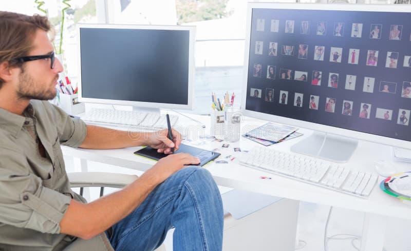 Fotoredaktör som använder digitizeren för att redigera arkivbild