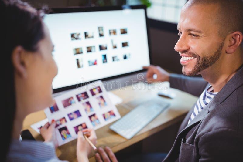 Fotoredaktörer som ler, medan diskutera över datoren arkivfoton