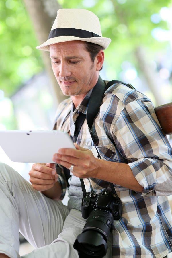 Fotoreporter som använder minnestavlan i stad arkivfoton