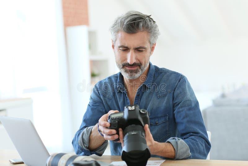 Fotoreporter som arbetar på kontoret fotografering för bildbyråer