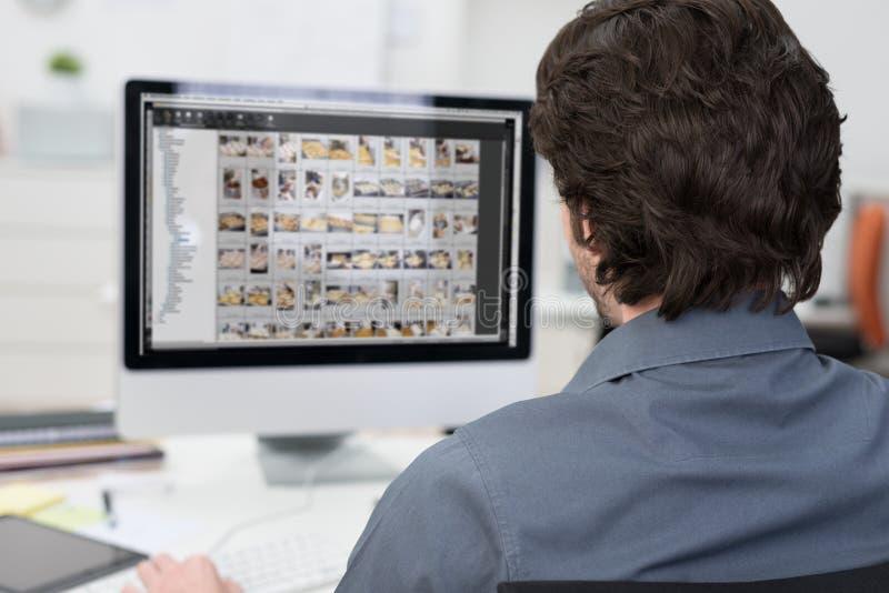 Fotos da edição do fotógrafo em um computador imagem de stock