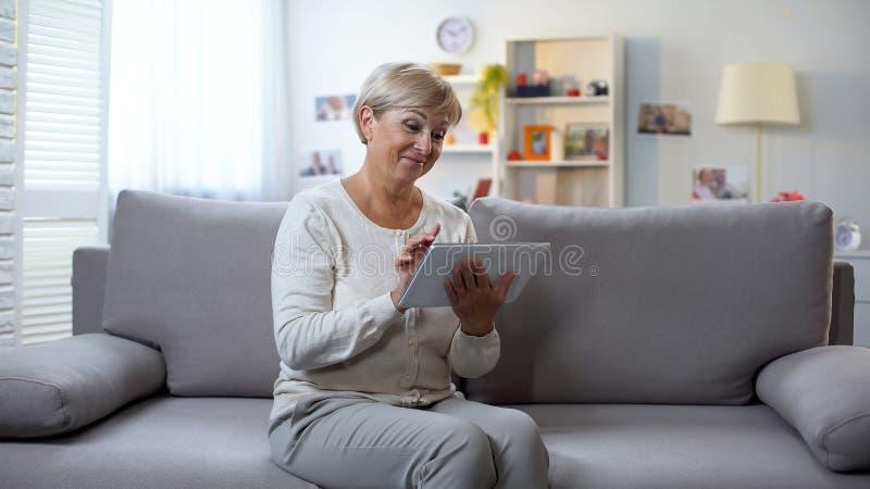 Fotos de observação envelhecidas felizes da mulher na tabuleta e no sorriso, passando o tempo livre foto de stock royalty free