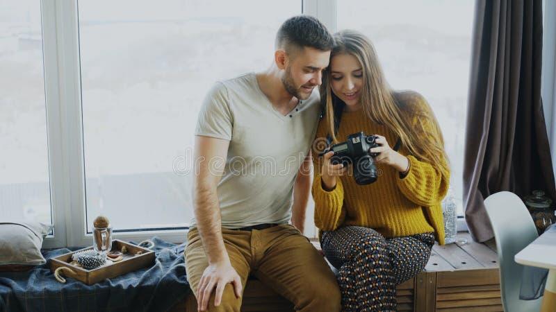 Fotos de observação de sorriso felizes dos pares do curso na câmara digital em casa após férias fotografia de stock royalty free