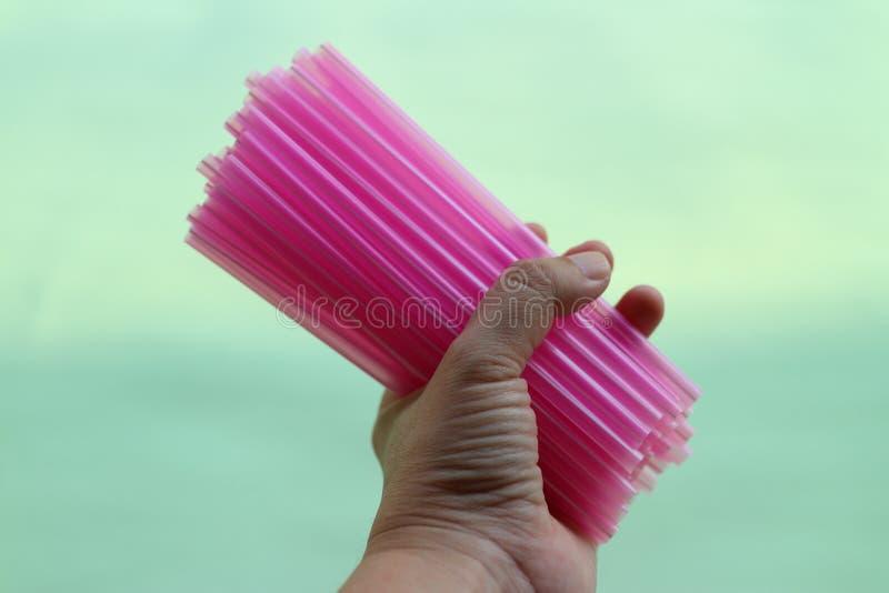 Fotos del primer de las mujeres que sostienen un tubo plástico rosado, conceptos de papel solos, en colores pastel del fondo de u fotos de archivo libres de regalías