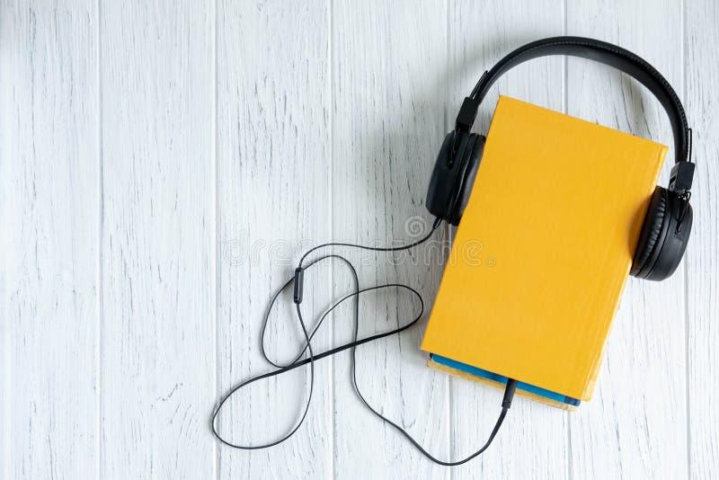 Fotos do livro e dos fones de ouvido conectados a ele Livro audio Foto conceptual no assunto do ensino ? dist?ncia Escuta imagem de stock