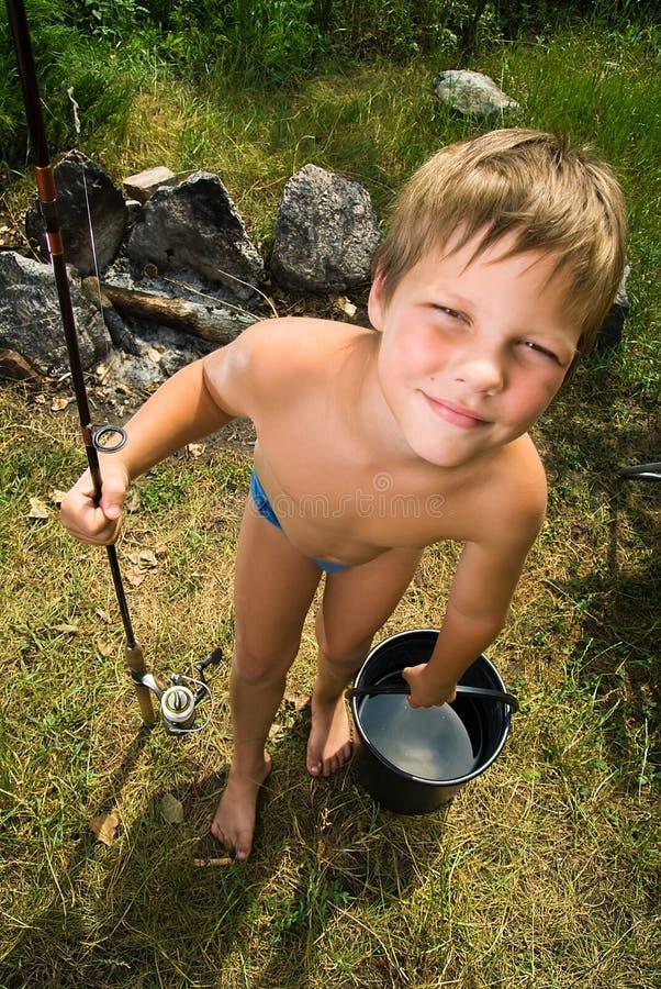 Fotos do menino com uma cubeta e uma haste de pesca fotografia de stock royalty free