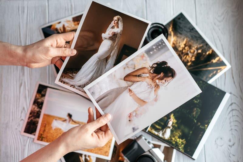 Fotos impressas do casamento com os noivos, uma câmera do preto do vintage e mãos da mulher com duas fotos imagens de stock