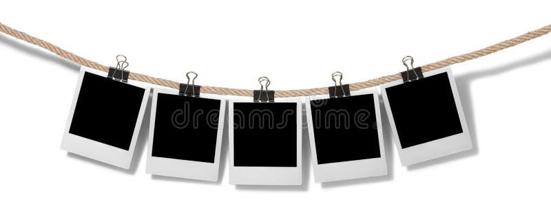 Fotos inmediatas en blanco que cuelgan en la cuerda para tender la ropa imagenes de archivo