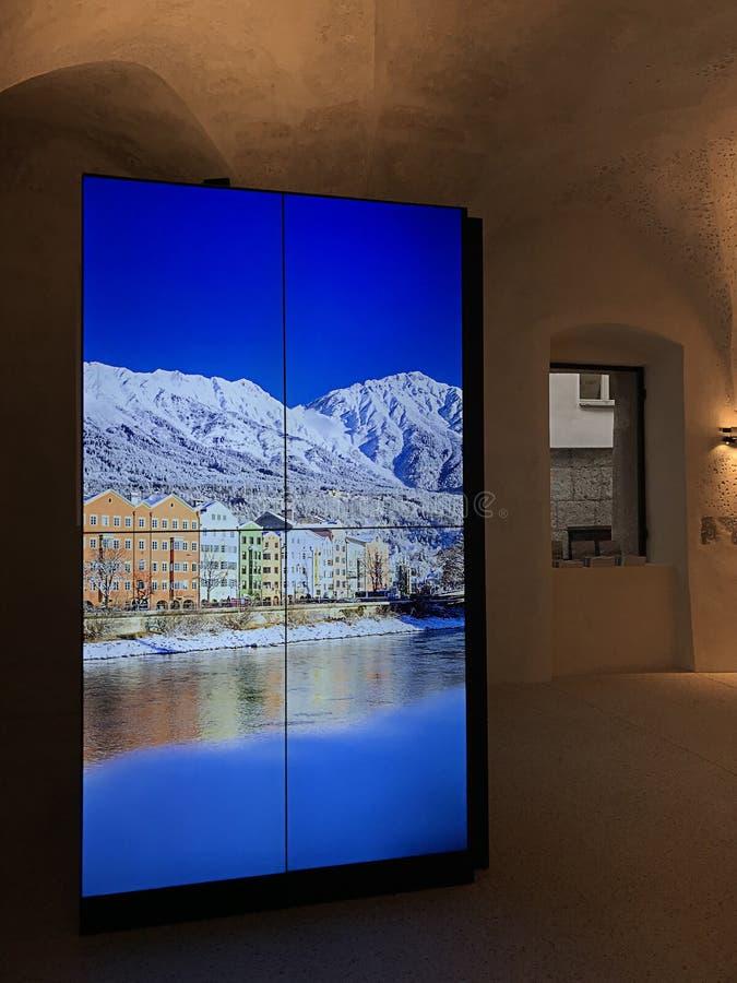 Fotos von schönen Pastellgebäuden entlang dem Fluss Gasthaus angezeigt auf der Großleinwand von Touristeninformations-Innsbruck-B stockfotografie