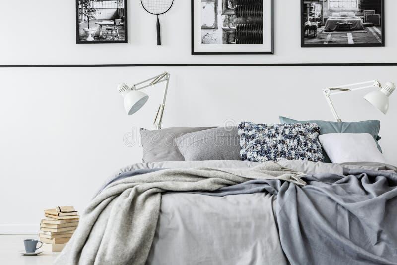 Fotosamlaresovrum med konungformatsäng med grå sängkläder och vita lampor, hög av böcker på golvet royaltyfria foton