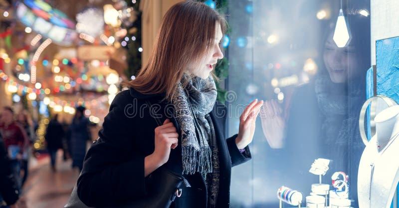 Fotoseite des jungen Brunette am Geschäftsfenster am Abend lizenzfreies stockbild