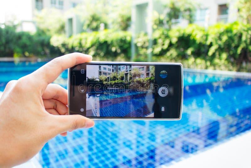 Fotoskytte på smartphonen på simbassängen arkivfoton